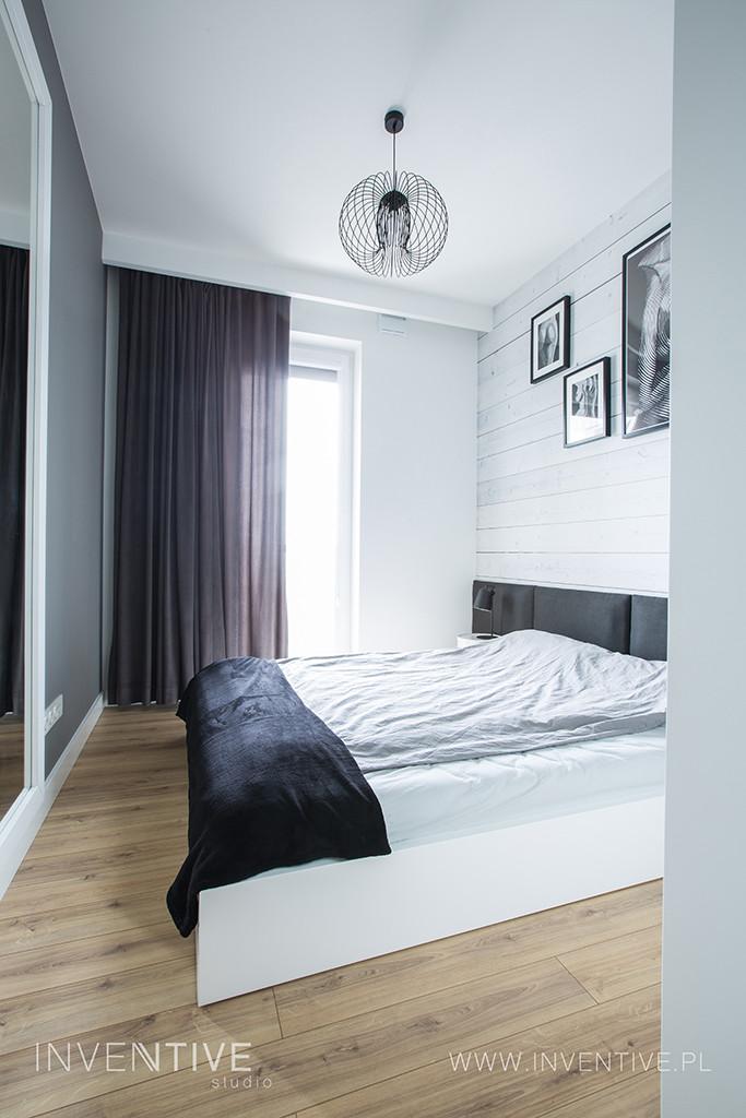 Sypialnia z białym, drewnianym łóżkiem kontynentalnym