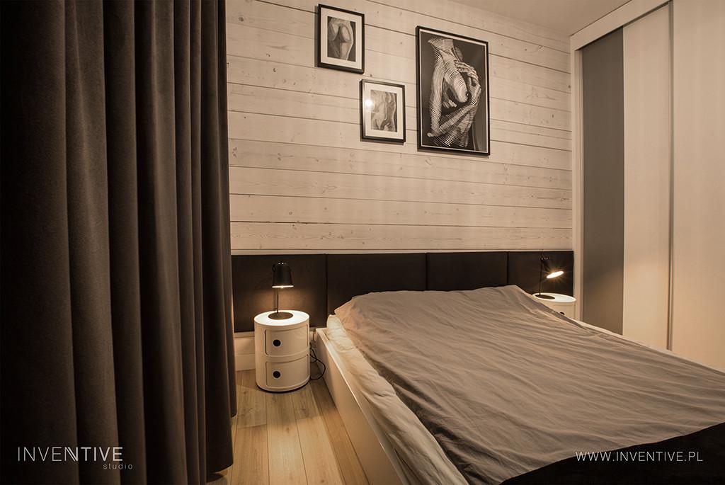 Sypialnia z jasnymi drewnianymi deskami na ścianie