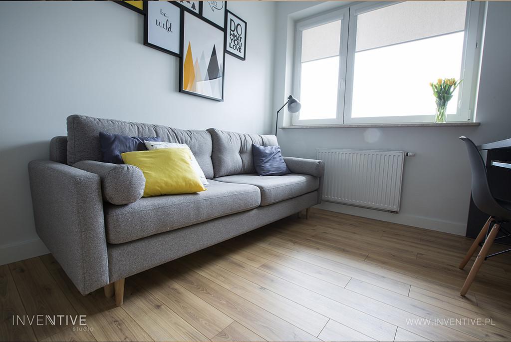 Szara, klasyczna sofa w pokoju studenta