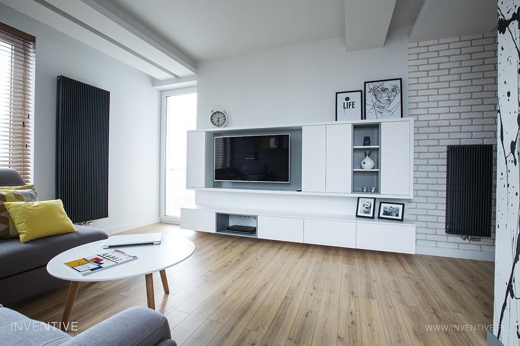 Salon z meblościanką i telewizorem na ścianie