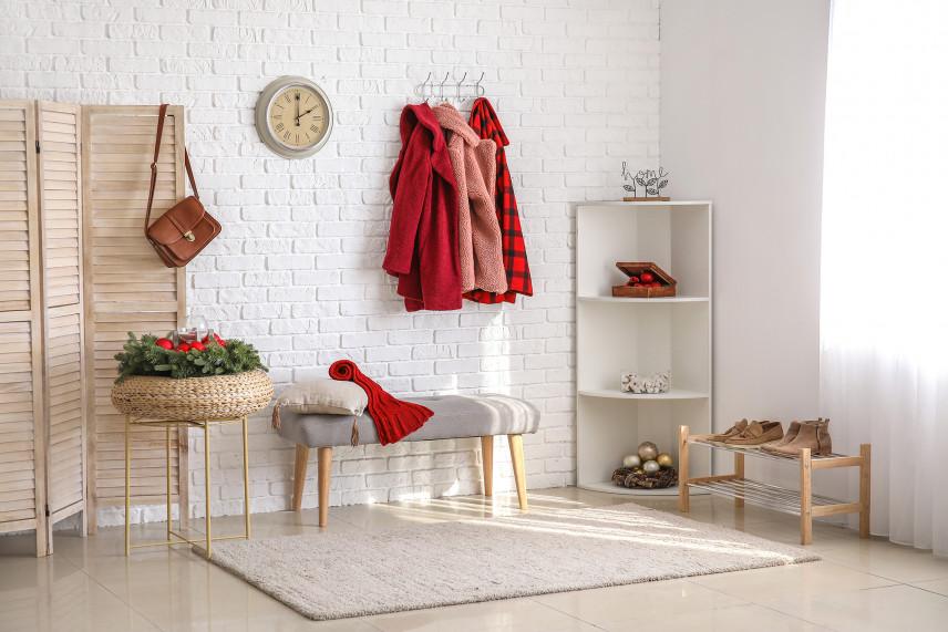 Jasny przedpokój z białą cegłą na ścianie