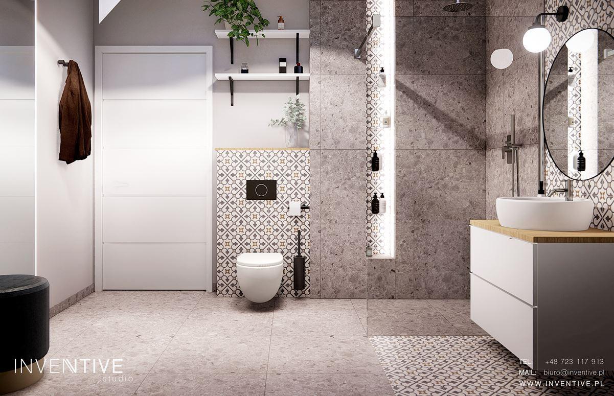Łazienka z szara podłogą, przeplatana płytkami z czarno-białą mozaiką