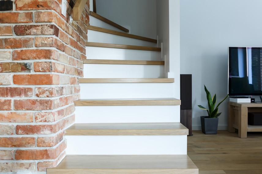 Białe schody z ceglaną ścianą